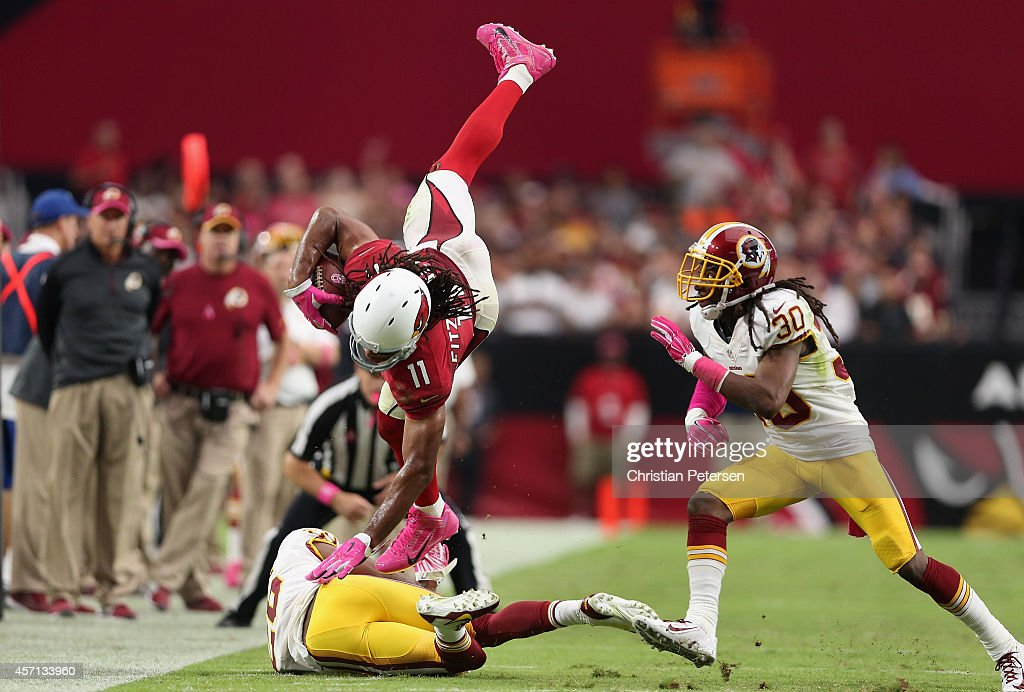 Wide receiver Larry Fitzgerald #11 of the Arizona Cardinals leaps over strong safety Bashaud Breeland #26 of the Washington Redskins after a reception during the fourth quarter of the NFL game at the University of Phoenix Stadium on October 12, 2014 in Glendale, Arizona. The Cardinals defeated the Redskins 30-20.