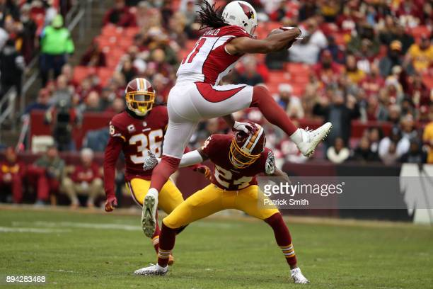 Wide Receiver Larry Fitzgerald of the Arizona Cardinals leaps over cornerback Josh Norman of the Washington Redskins in the first quarter at FedEx...