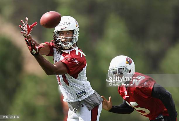 Wide receiver Larry Fitzgerald of the Arizona Cardinals makes a reception past safety Kerry Rhodes during the team training camp at Northern Arizona...