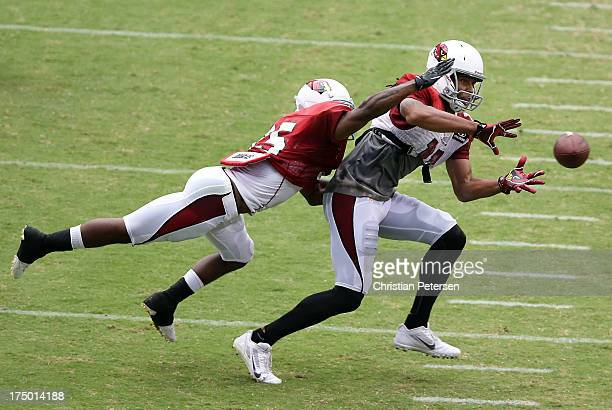 Wide receiver Larry Fitzgerald of the Arizona Cardinals makes a reception past cornerback Javier Arenas during the team training camp at University...