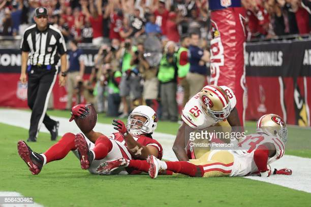 Wide receiver Larry Fitzgerald of the Arizona Cardinals reacts after scoring the gamewinning touchdown over cornerback Rashard Robinson and...