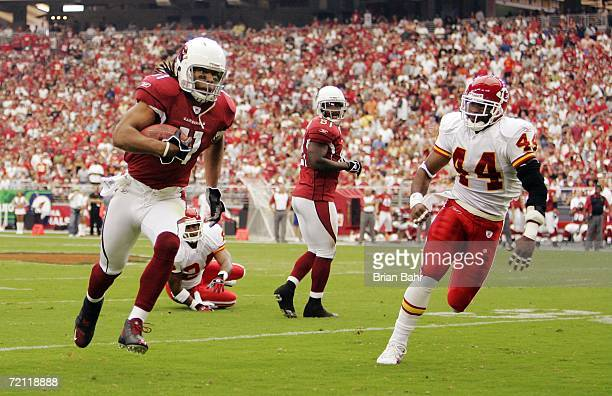 Wide receiver Larry Fitzgerald of the Arizona Cardinals runs around the outside toward the endzone against safety Jarrad Page of the Kansas City...