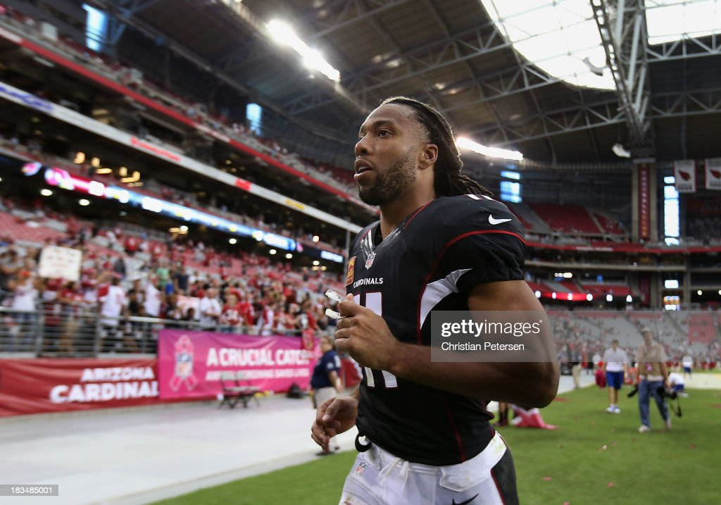Wide receiver Larry Fitzgerald #11 of the Arizona Cardinals runs off the field following the NFL game against the Carolina Panthers at the University of Phoenix Stadium on October 6, 2013 in Glendale, Arizona. The Cardinals defeated the Panthers 22-6.