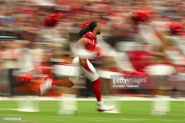 Wide receiver Larry Fitzgerald of the Arizona Cardinals runs onto the field during introductions to the NFL game against the Washington Redskins at...