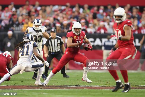 Wide receiver Larry Fitzgerald of the Arizona Cardinals runs with the football after a reception against defensive back Marqui Christian of the Los...