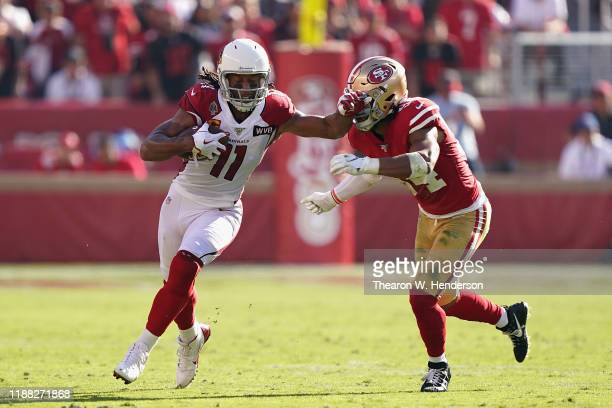 Wide receiver Larry Fitzgerald of the Arizona Cardinals runs with the football after a reception past linebacker Fred Warner of the San Francisco...