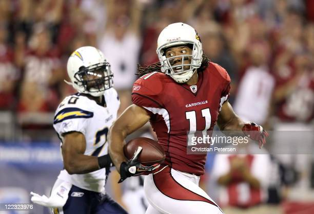 Wide receiver Larry Fitzgerald of the Arizona Cardinals runs with the ball on a 80 yard touchdown reception past cornerback Antoine Cason of the San...