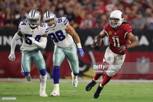 Wide receiver Larry Fitzgerald of the Arizona Cardinals runs with the football after a reception ahead of outside linebacker Jaylon Smith and...