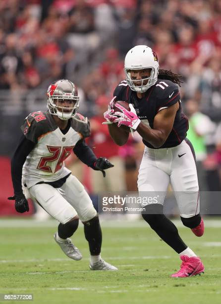 Wide receiver Larry Fitzgerald of the Arizona Cardinals runs with the football after a reception past cornerback Vernon Hargreaves of the Tampa Bay...