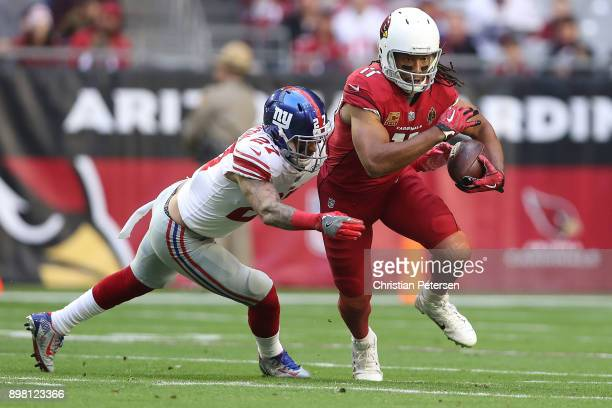 Wide receiver Larry Fitzgerald of the Arizona Cardinals runs with the football against free safety Darian Thompson of the New York Giants in the...