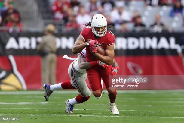 Wide receiver Larry Fitzgerald of the Arizona Cardinals runs with the football after a reception past free safety Darian Thompson of the New York...