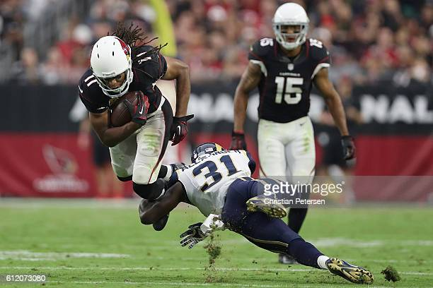 Wide receiver Larry Fitzgerald of the Arizona Cardinals rushes the football against free safety Maurice Alexander of the Los Angeles Rams during the...