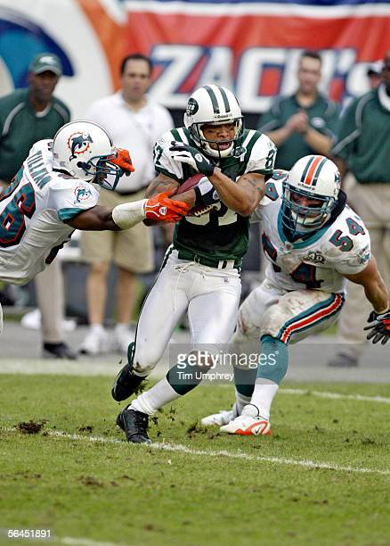 Wide receiver Laveranues Coles of the New York Jets tries to break the tackle of Safety Travares Tillman and Linebacker Zach Thomas of the Miami...