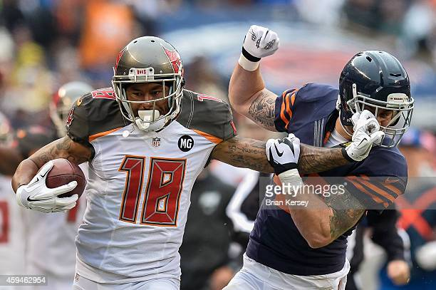 Wide receiver Louis Murphy of the Tampa Bay Buccaneers carries for 54 yards but receives a penalty for holding onto the face mask of Chris Conte of...