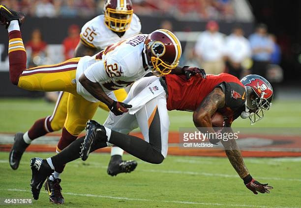 Wide receiver Louis Murphy of the Tampa Bay Buccaneers is tackled by cornerback Tracy Porter of the Washington Redskins at Raymond James Stadium on...