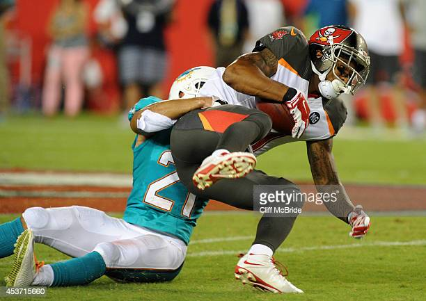 Wide receiver Louis Murphy of the Tampa Bay Buccaneers is taken down by Cornerback Brent Grimes of the Miami Dolphins in first half action at Raymond...
