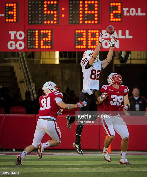 Wide receiver Luke Austin of the Idaho State Bengals reaches for a pass over cornerback Jase Dean and safety Justin Blatchford of the Nebraska...