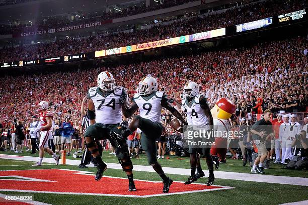 Wide receiver Malcolm Lewis and offensive linesman Ereck Flowers of the Miami Hurricanes celebrate after scoring during their game against the...