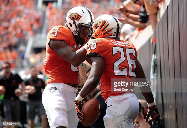 Wide receiver Marcell Ateman congratulates running back Barry Sanders of the Oklahoma State Cowboys after a score against the Southeastern Louisiana...