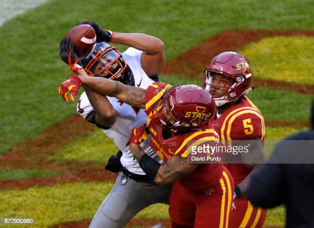 Wide receiver Marcell Ateman of the Oklahoma State Cowboys pulls in a touchdown pass as defensive back D'Andre Payne and defensive back Kamari...