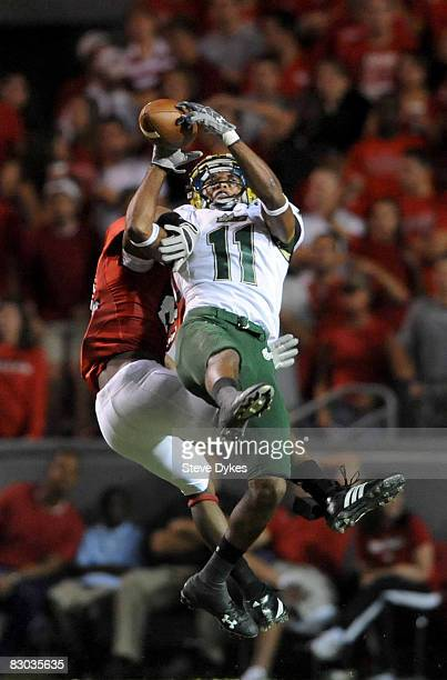 Wide receiver Marcus Edwards of the South Florida Bulls goes up high to catch a pass for a long gain as DeAndre Morgan of the North Carolina State...