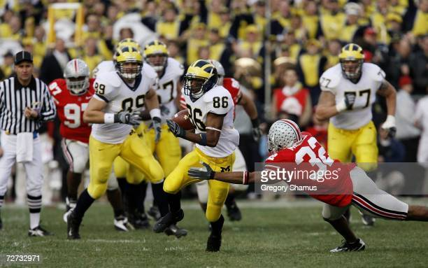 Wide receiver Mario Manningham of the Michigan Wolverines runs with the ball against safety Brandon Mitchell of the Ohio State Buckeyes on November...