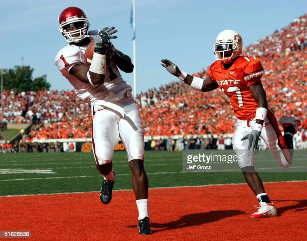 Wide receiver Mark Bradley of Oklahoma catches a touchdown pass in front of safety Jon Holland of Oklahoma State in the first quarter at Boone...