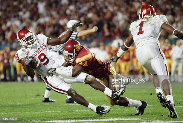 Wide receiver Mark Clayton of the Oklahoma Sooners is hit hard by Justin Wyatt of the USC Trojans after catching a pass in the second quarter during...