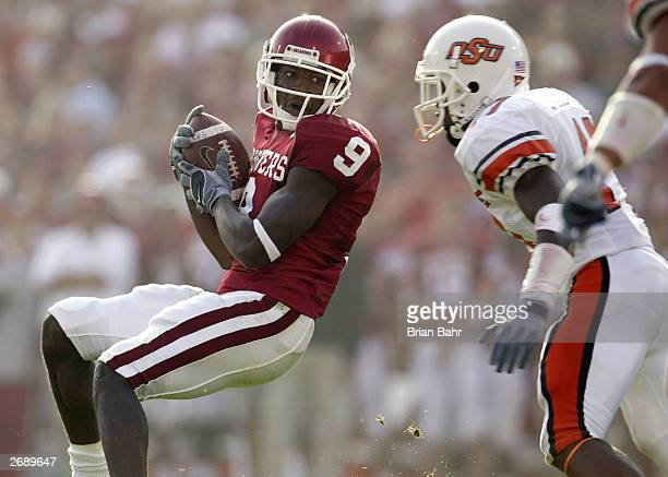 Wide receiver Mark Clayton of the Oklahoma Sooners pulls in a long pass against defensive back Jon Holland of the Oklahoma State Cowboys in the...