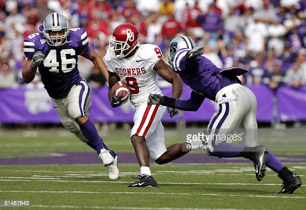 Wide receiver Mark Clayton of the Oklahoma Sooners slips between linebacker Brandon Archer and defensive back Cedrick Williams of the Kansas State...