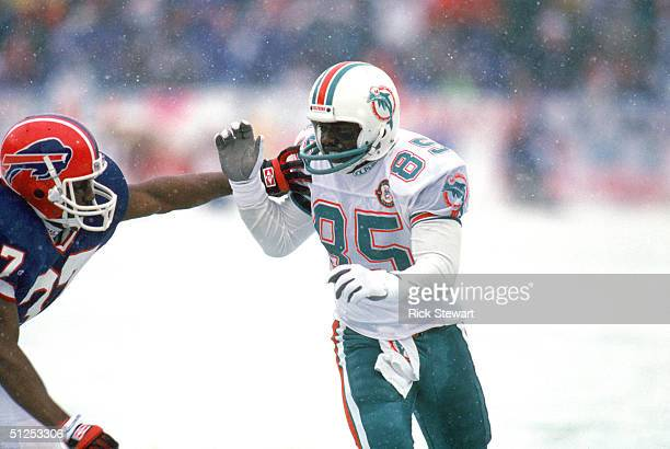 Wide receiver Mark Duper of the Miami Dolphins battles with a Buffalo Bills defender in the 1991 AFC Divisional Playoff game at Ralph Wilson Stadium...