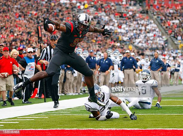 Wide receiver Mark Harrison of the Rutgers Scarlet Knights slips out of the grasp of Andrew Adams of the Connecticut Huskies as he jumps into the end...