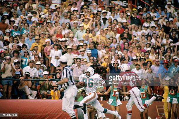 Wide receiver Marlin Briscoe of the Miami Dolphins runs the ball down the sidelines as defensive back Ron Bolton of the New England Patriots tries to...