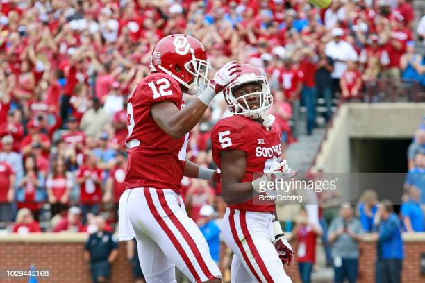 Wide receiver Marquise Brown is congratulated by wide receiver AD Miller of the Oklahoma Sooners after scoring a touchdown against the UCLA Bruins at...
