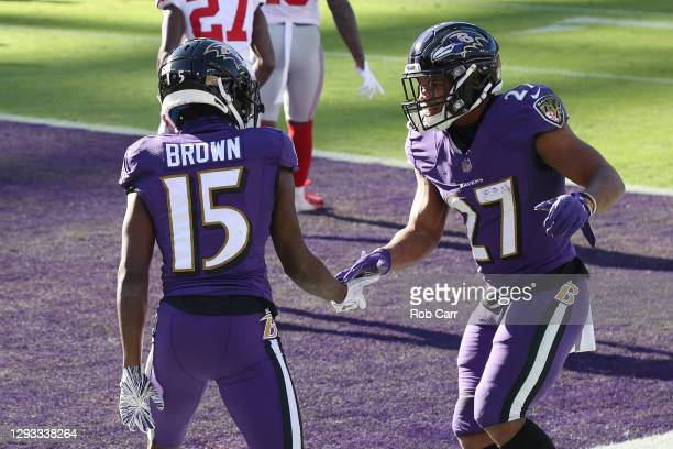Wide receiver Marquise Brown of the Baltimore Ravens celebrates a touchdown catch with teammate J.K. Dobbins during the first quarter against the New...