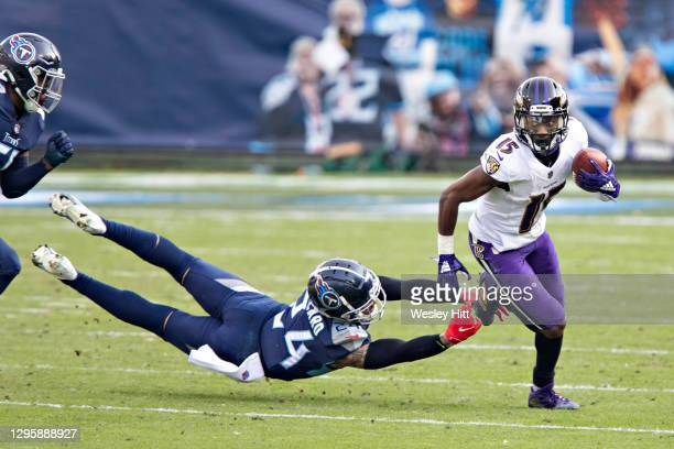 Wide receiver Marquise Brown of the Baltimore Ravens runs the ball during their AFC Wild Card Playoff game and avoids the tackle of safety Kenny...