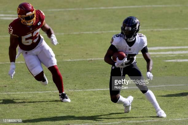 Wide receiver Marquise Brown of the Baltimore Ravens runs with the ball after catching a pass in front of inside linebacker Jon Bostic of the...