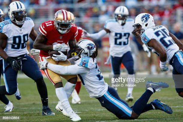 Wide receiver Marquise Goodwin of the San Francisco 49ers is tackled by strong safety Johnathan Cyprien of the Tennessee Titans during the fourth...