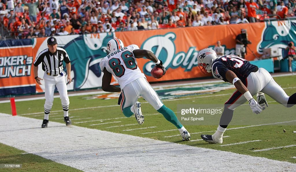 Wide receiver Marty Booker #86 of the Miami Dolphins catches a deep sideline pass to set up a game clinching touchdown while covered by cornerback Chad Scott #30 of the New England Patriots at Dolphin Stadium on December 10, 2006 in Miami, Florida. The Dolphins defeated the Patriots 21-0.