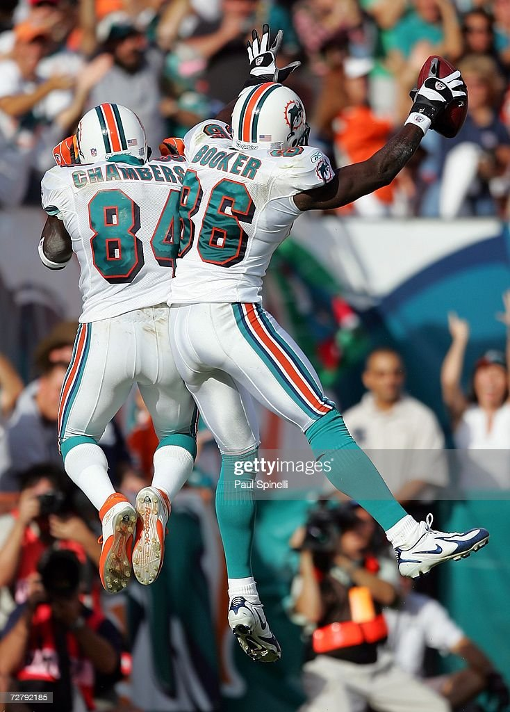 Wide receiver Marty Booker #86 of the Miami Dolphins jumps in celebration and does a hip bump with teammate Chris Chambers #84 after Booker catches a touchdown pass for a 13-0 lead against the New England Patriots at Dolphin Stadium on December 10, 2006 in Miami, Florida. The Dolphins defeated the Patriots 21-0.