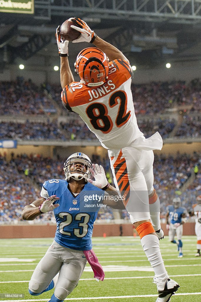 Wide receiver Marvin Jones #82 of the Cincinnati Bengals catches a touchdown pass while under pressure from cornerback Chris Houston #23 of the Detroit Lions during the first half at Ford Field on October 20, 2013 in Detroit, Michigan.