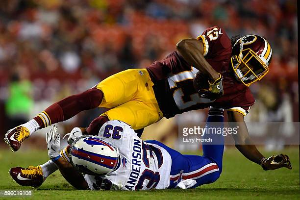 Wide receiver Maurice Harris of the Washington Redskins runs the ball while defensive back Colt Anderson of the Buffalo Bills defends during the game...