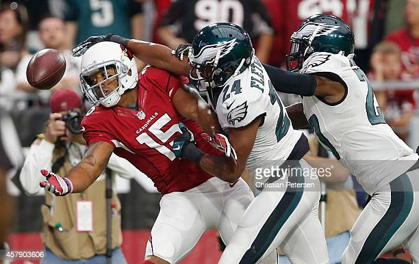 Wide receiver Michael Floyd of the Arizona Cardinals attempts to make a catch against cornerback Bradley Fletcher and free safety Malcolm Jenkins of...