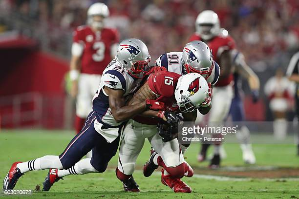 Wide receiver Michael Floyd of the Arizona Cardinals makes a reception against cornerback Malcolm Butler and outside linebacker Jamie Collins of the...