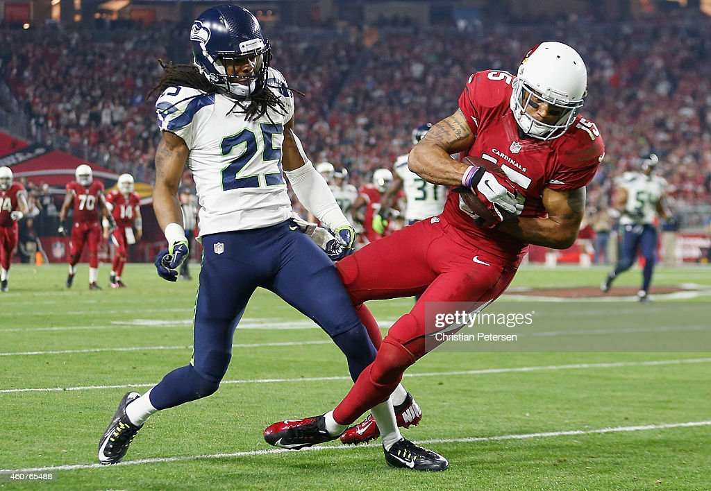 Wide receiver Michael Floyd #15 of the Arizona Cardinals makes a reception past cornerback Richard Sherman #25 of the Seattle Seahawks in the third quarter during the NFL game at the University of Phoenix Stadium on December 21, 2014 in Glendale, Arizona.