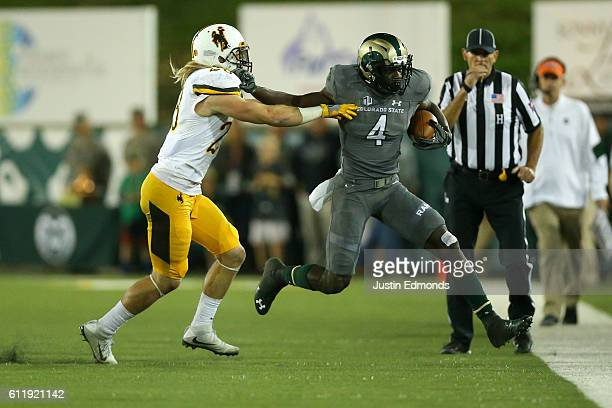 Wide receiver Michael Gallup of the Colorado State Rams applies a stiff arm to safety Andrew Wingard of the Wyoming Cowboys as he is forced out of...