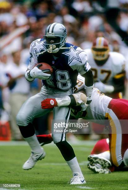 Wide Receiver Michael Irvin of the Dallas Cowboys is wrapped up by linebacker Rod Stephens of the Washington Redskins October 1 1995 during an NFL...