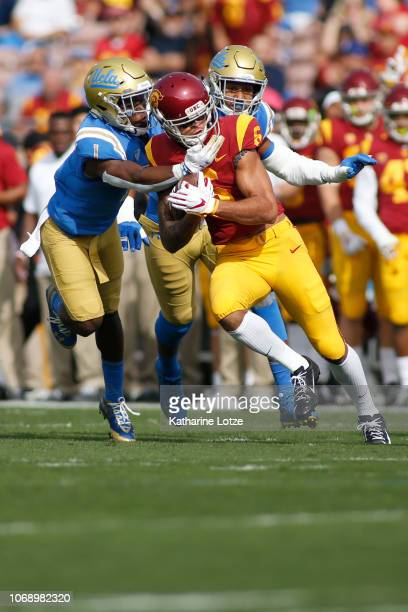 Wide receiver Michael Pittman Jr #6 of the USC Trojans carries the ball down the field as defensive back Darnay Holmes of the UCLA Bruins tackles...