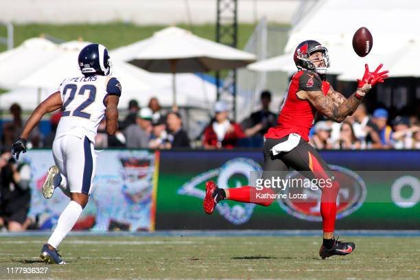 Wide receiver Mike Evans of the Tampa Bay Buccaneers catches a pass before running it in for a touchdown as cornerback Marcus Peters of the Los...