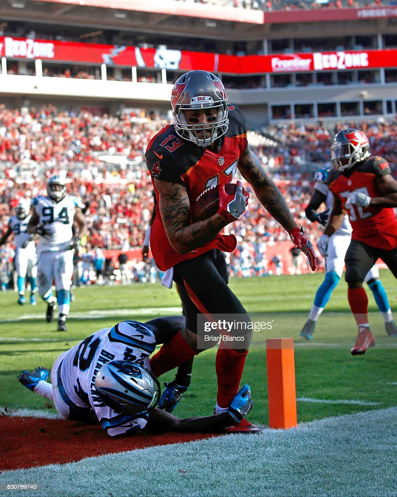 Wide receiver Mike Evans #13 of the Tampa Bay Buccaneers hauls in a 10 yard pass from quarterback Jameis Winston for the touchdown while getting pressure from cornerback James Bradberry #24 of the Carolina Panthers during the fourth quarter of an NFL game on January 1, 2017 at Raymond James Stadium in Tampa, Florida.
